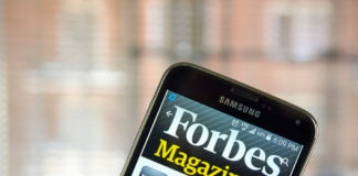 Phone with Forbes Magazine application open.