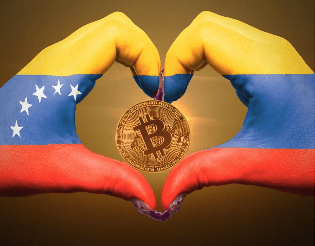 Hands make a shape of a heart around a bitcoin, painted with the colours of Venezuela's national flag.