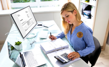 A woman with a Bitcoin badge makes calculations at a desk.