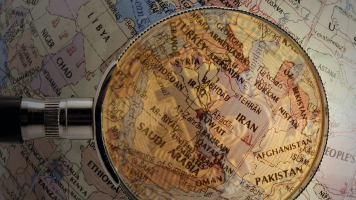 A magnifying glass hovers over a map of Central Asia.