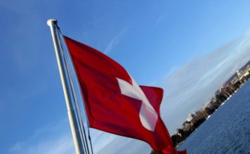 switzerland flag with city and lake in the background